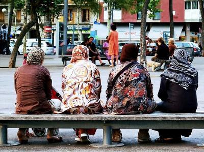 vier Frauen mit Kopftuch sitzen auf einer Bank