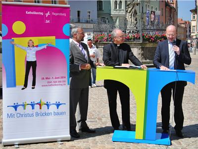 drei Männer präsentieren das Logo des Katholikentages 2014