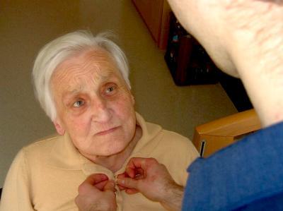 ein Freiwilliger hilft einer alten Dame beim Anziehen