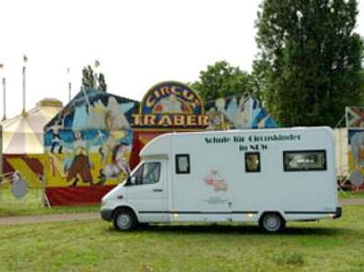 ein Fahrzeug der Schule für Zirkuskinder vor einem Zirkuszelt