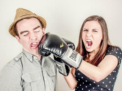 Frau mit Boxhandschuh schlägt Mann
