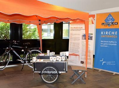 Ein Fahrrad mitsamt Anhänger, Sonnenpavillion, Hockern und Café-Ausrüstung