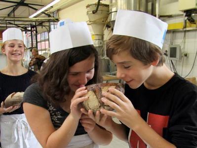 zwei Jugendliche mit Bäckermützen schnuppern an einem Laib Brot