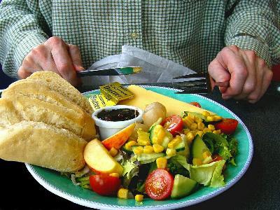 Mann sitzt mit Messer und Gabel vor einem gefüllten Teller