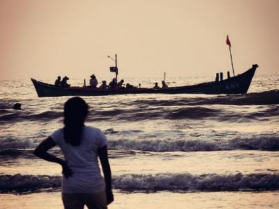 Mädchen am Strand beobachtet das Ablegen eines Flüchtlingsbootes