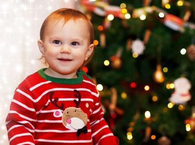 lachendes Kleinkind vor einem geschmückten Weihnachtsbaum
