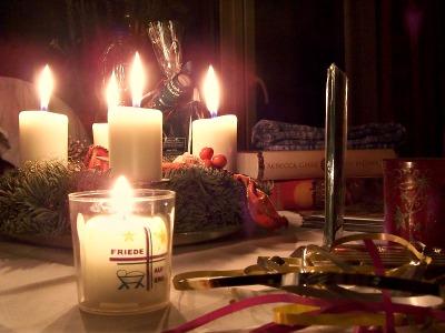 weihnachtlicher Tisch mit Adventskranz und brennenden Kerzen