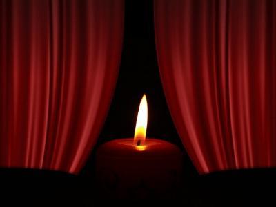 Kerzenlicht vor einem geöffneten roten Samtvorhang
