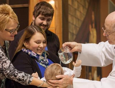 Priester und eine Familie mit Kleinkind am Taufbecken