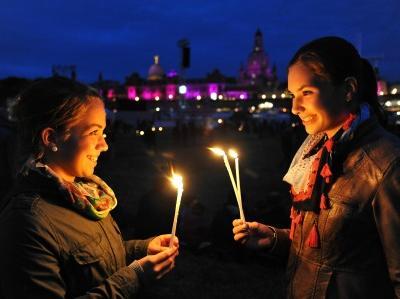 zwei junge Frauen mit brennenden Kerzen vor der nächtlichen Skyline von Dresden