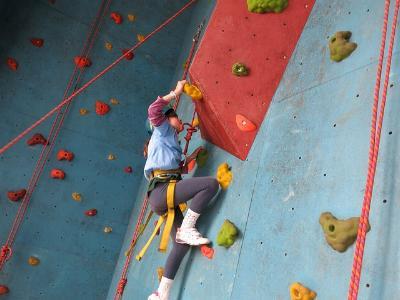 Jugendlicher klettert an einer künstlichen Kletterwand nach oben