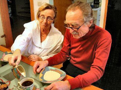 Mann und Frau am Tisch, sie schüttet ihm Milch in den Kaffee