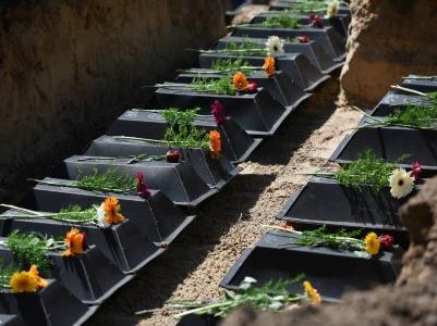 Pappsärge mit den Überresten deutscher Gefallener werden in einem Gemeinschaftsgrab beigesetzt.