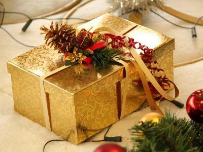 ein Weihnachtsgeschenk in einem goldenen Karton verpackt