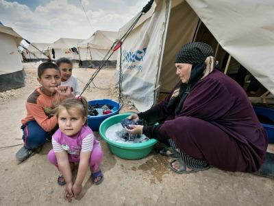Frau mit Kindern vor einem Zelt im jordanischen Flüchtlingslager Zaatari