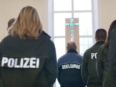 Polizistinnen und Polizisten in Uniform bei einem Gottesdienstbesuch.