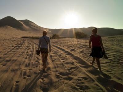 zwei Frauen durchwandern eine Sandwüste