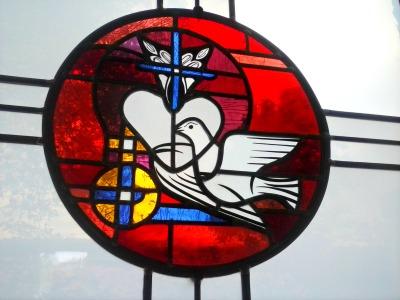 buntes Kirchenfenster mit weißer Taube auf rotem Hintergrund