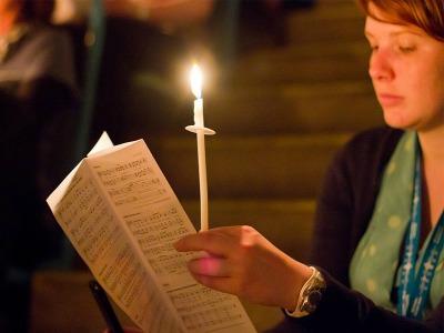 andächtige junge Frau mit Kerze und Liedblatt