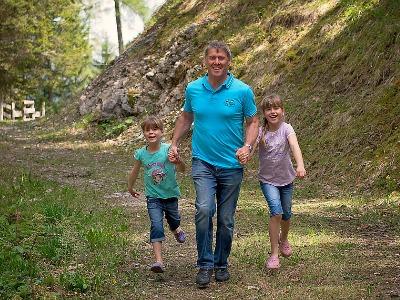 Vater mit zwei Töchtern rennen auf Waldweg