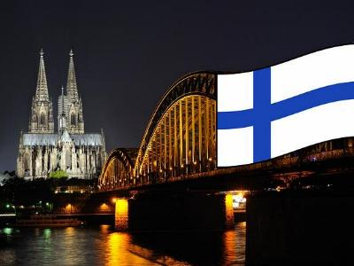 Kölner Dom und Deutzer Brücke bei Nacht mit finnischer Fahne