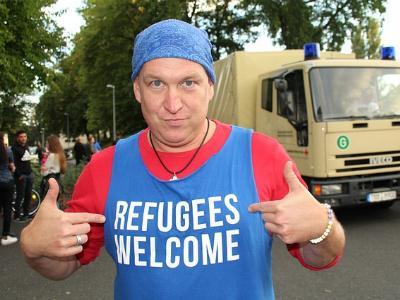 Mann mit blauem Shirt und Aufschrift 'Refugees wellcome'