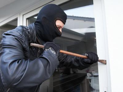 maskierter Einbrecher mit Brecheisen hebelt ein Fenster auf