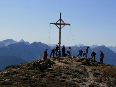 Menschen auf einem Berg, um ein Gipfelkreuz versammelt