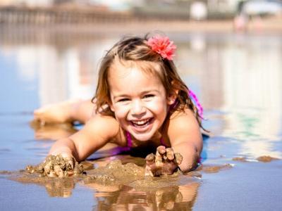 lachendes Mädchen liegt auf dem Bauch in einer Wasserpfütze