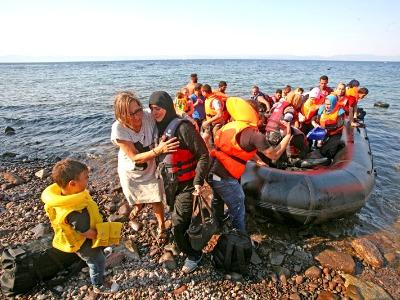 ein Schlauchboot mit Flüchtlingen kommt am Strand an