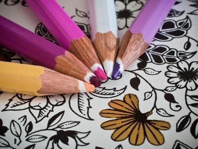 Buntstifte liegen auf einem Ausmalbuch
