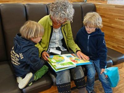 Frau und zwei Kinder lesen gemeinsam ein Buch