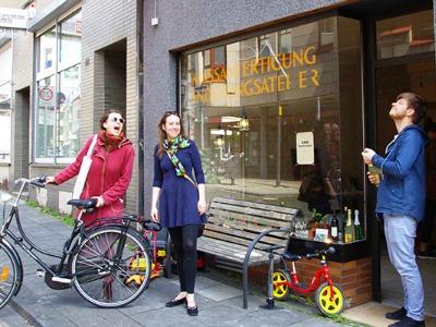 drei junge Menschen stehen vor einem alten Ladenlokal