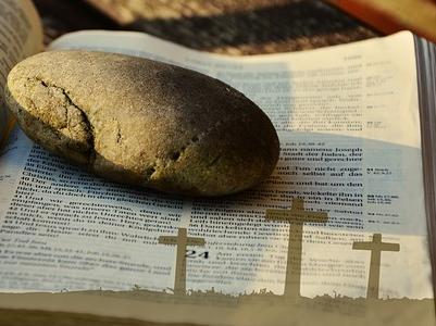Kreuze und ein Kieselstein liegen auf einer aufgeschlagenen Bibelseite
