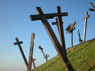 mehrere große Holzkreuze stehen ungeordnet auf einem grünen Hügel