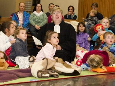 Pfarrerin im Talar sitzt mit Kindern auf dem Boden