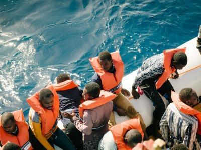 Blick von oben auf Flüchtlinge mit Schwimmwesten in einem Schlauchboot
