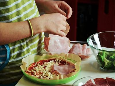 Kinderhände belegen eine Pizza mit Zutaten