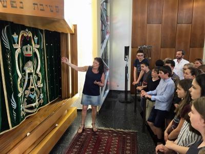 Frau erklärt Jugendlichen das Innere einer Synagoge