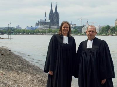 Ein Pfarrer und eine Pfarrerin im Talar am Rheinufer, im Hintergrund der Kölner Dom