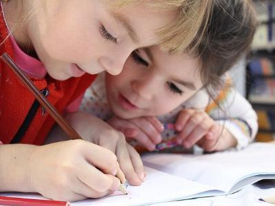 zwei Grundschülerinnen machen Hausaufgaben