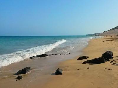 Sanfte Wellen treffen auf einen weitläufigen Sandstrand