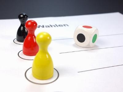 Spielfiguren in schwarz, rot und gelb auf einem Wahlzettel