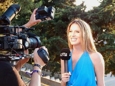 junge Reporterin mit Mikrofon steht vor Kameras
