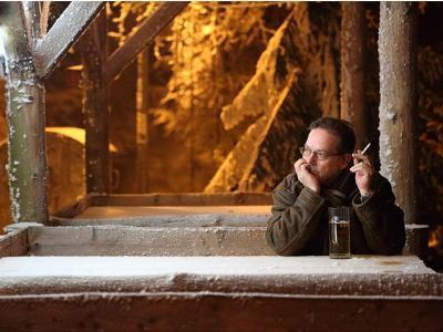 einsamer Mann mit Zigarette und Bier auf einer Holzbank