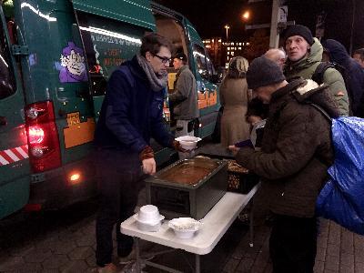 Helfer schenkt warme Suppe an Obdachlose aus