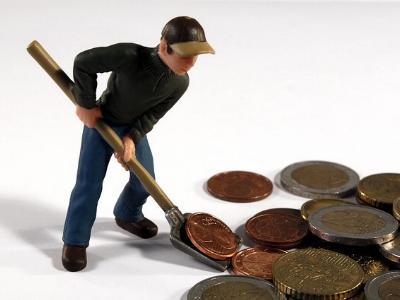 Spielfigur schaufelt Euro-Münzen