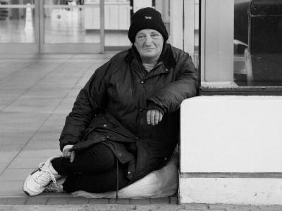 obdachlose Frau sitzt auf dem Boden