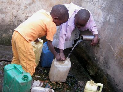 zwei afrikanische Kinder mit Wasserkanistern an einem Brunnen