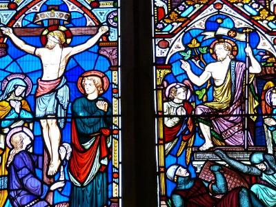 buntes Kirchenfenster zeigt als Motive die Kreuzigung und Auferstehung Jesu